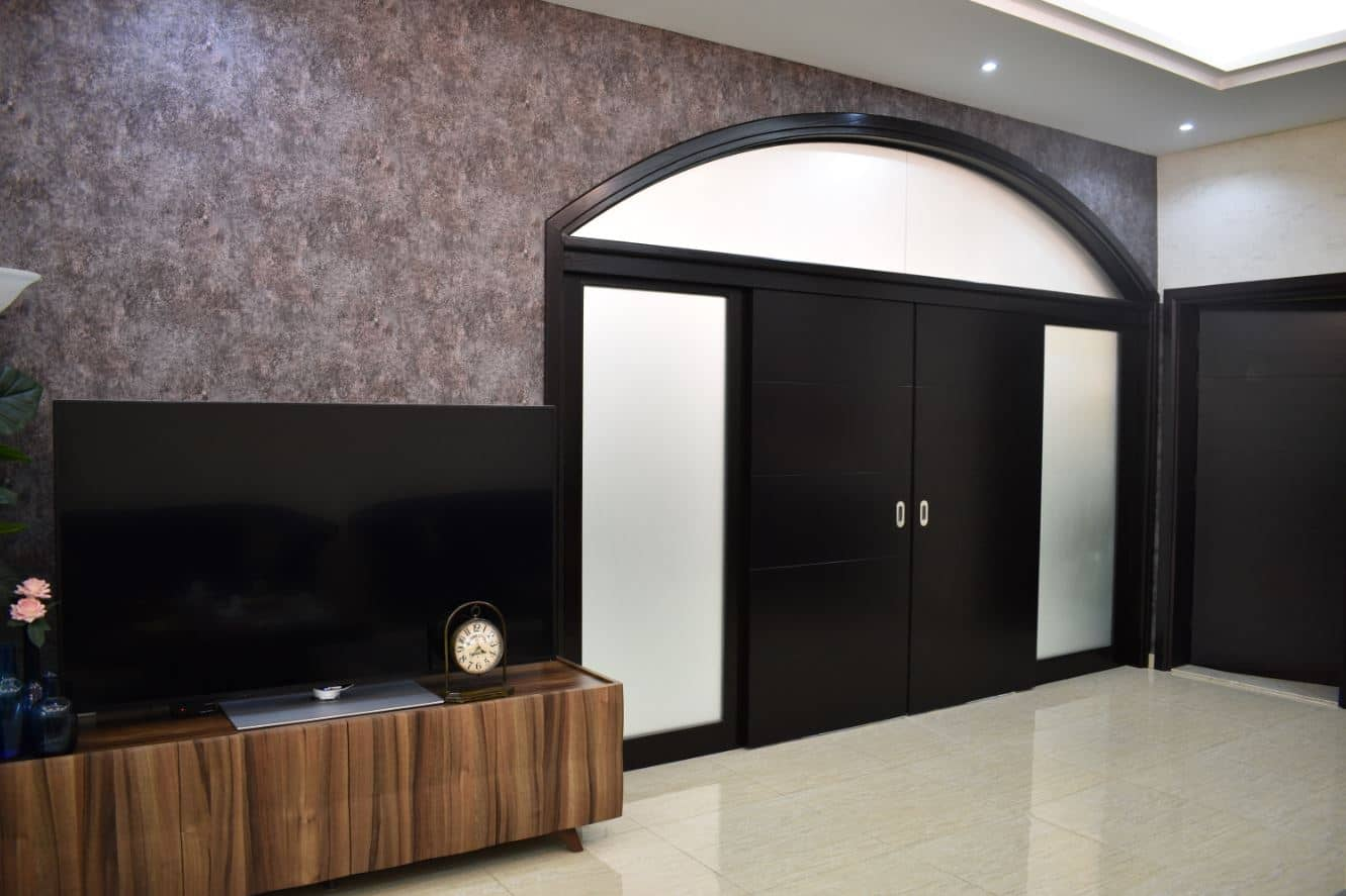 Manufacturing of meranti solid wooden sliding door with sand blasted glass frames around. The door was polished dark mahogany. Along with it was also manufactured a full height frame using ash crown veneer polished dark mahogany for a villa in Mirdif, Dubai.