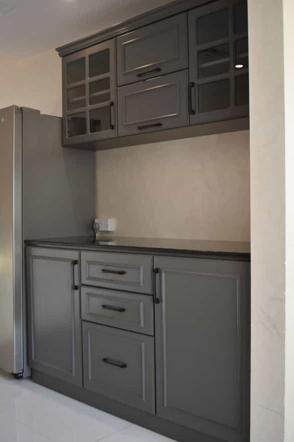 Manufacturing of small pantry for second floor of Villa in Al Warqa'a, Dubai. The pantry was made using plain MDF painted matte grey with lower cabinet consisting of doors and drawers with marble top along with upper cabinetry installed with wooden panel doors induced with glass inside and hydraulics.