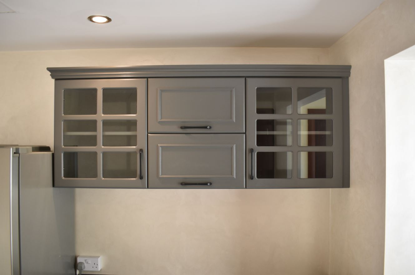 The pantry was painted matte grey consisting of drawer units, shelves and doors.