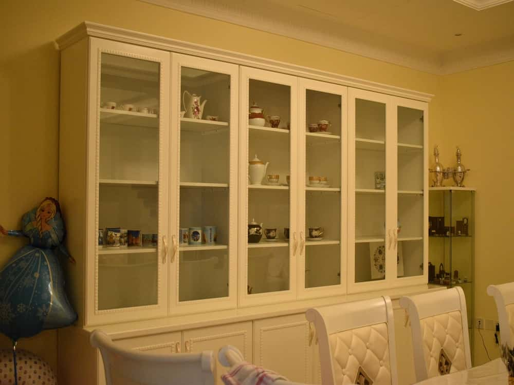 Manufacturing of decorative storage cabinet consisting of shelving, upper glass doors and lower hidden storage with antique moldings on top all painted beige color for a villa in hor al anz, deira, uae.