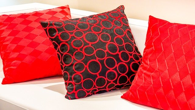 Red upholstered sofa cushions with design in it.